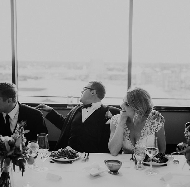 A bride and groom sitting in front of a window with a view of Louisville in Swizzle
