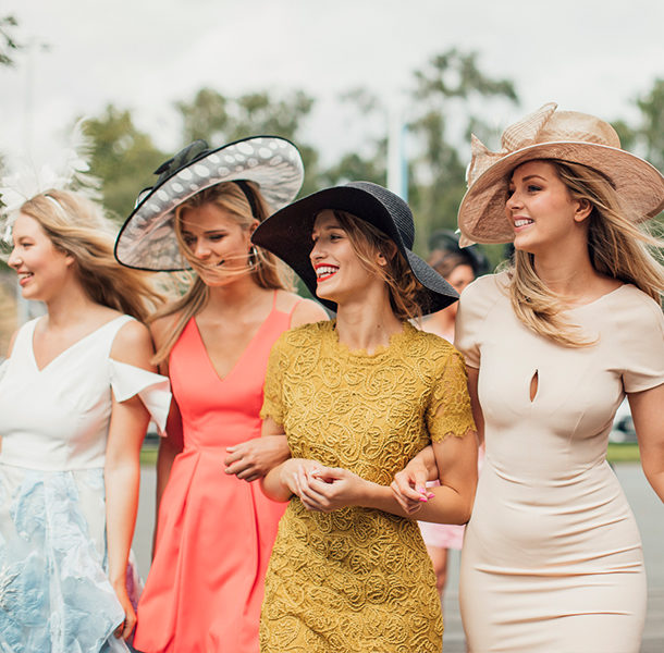 four women in kentucky derby fashions walking and smiling