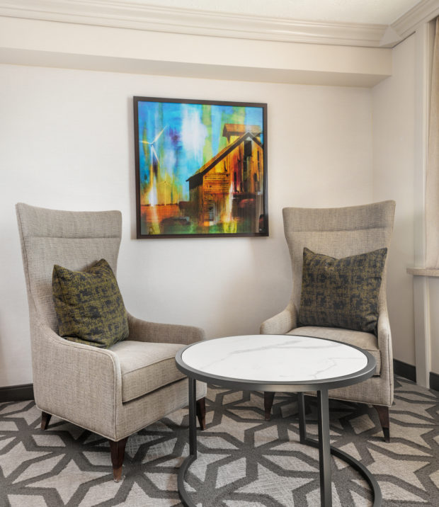 Two chairs at a small round table with a bright painting on the wall between them