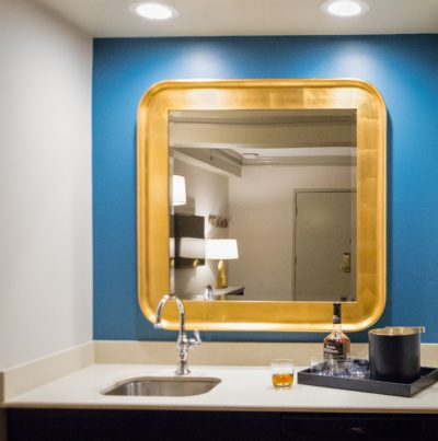 Rounded-corner square bathroom mirror in a blue wall.
