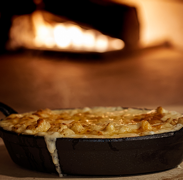 mac and cheese dish next to a wood-burning oven at walker's exchange restaurant