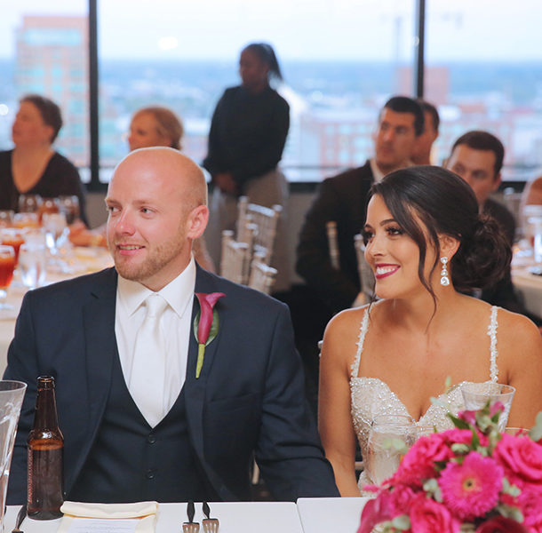 a bride and groom smiling sitting at a dinner table in the waterford room