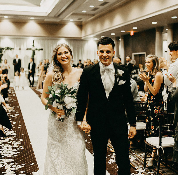 a bride and groom walking down the aisle in the Archibald Cochran room